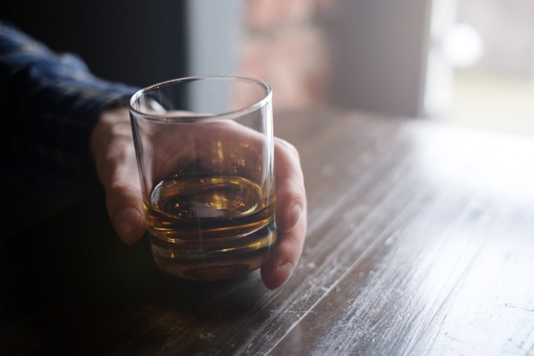 Image: Man holding glass of whiskey