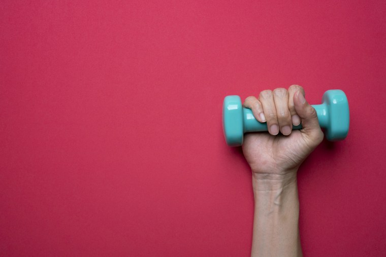 A woman holds a dumbbell
