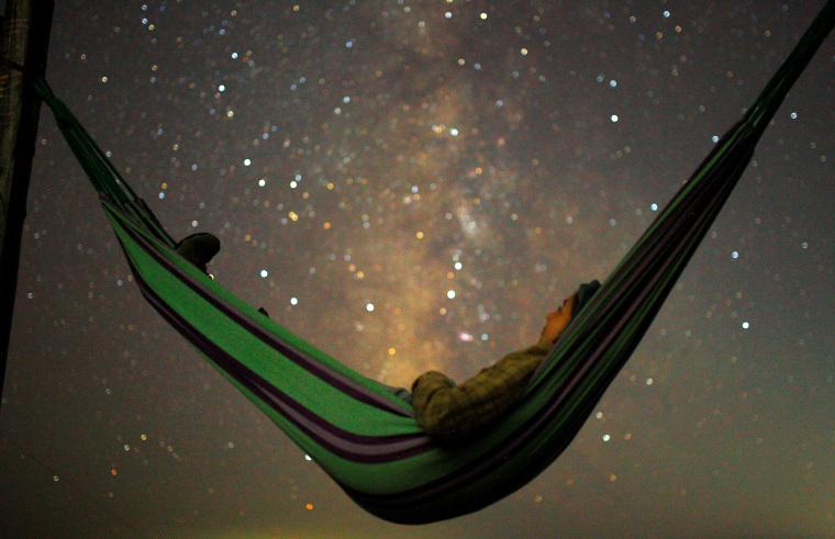 A girl lies in hammock as she looks at the milky way during the peak of Perseid meteor shower in Kozjak