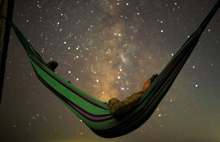 A girl lies in hammock as she looks at the milky way during the peak of Perseid meteor shower in Kozjak