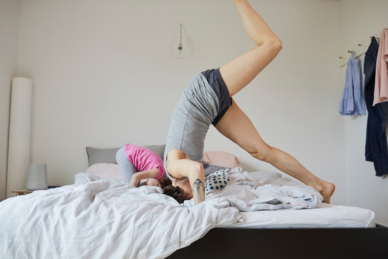 Image: Mother and daughter playing in bedroom, doing headstands
