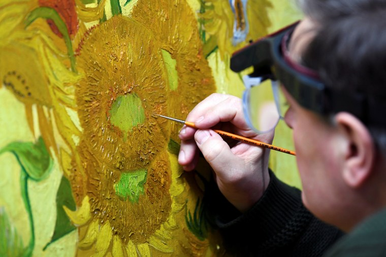 "Image: Renovator Rene Boitelle works on a restoration of Van Gogh's painting ""Sunflowers"" at Van Gogh Museum in Amsterdam"