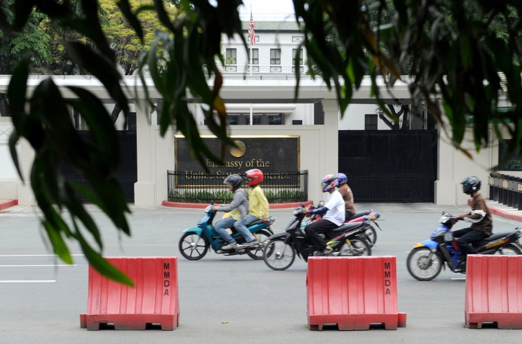 Image: Commuters pass the United States Embassy in Manila on July 6, 2013.