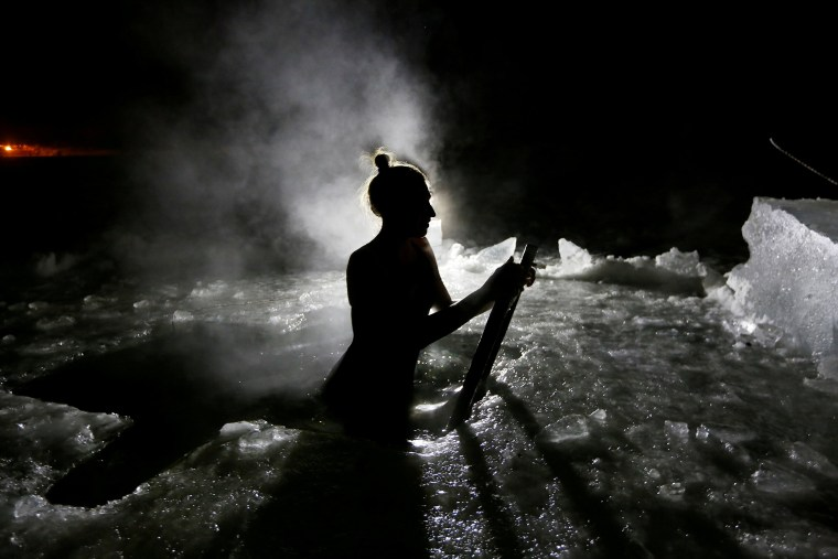 Image: A woman takes a dip in the icy waters of the Yenisei River during Epiphany celebrations outside Krasnoyarsk