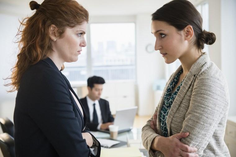 Businesswomen glaring at each other in office