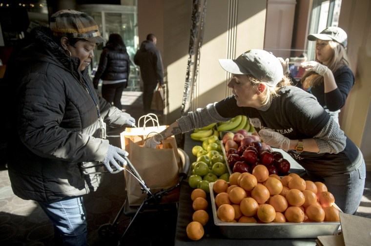 Image: Furloughed government worker Sarah Stella, with the USDA, hands out fruit to other furloughed government workers at the World Central Kitchen in Washington on Jan. 22, 2019.