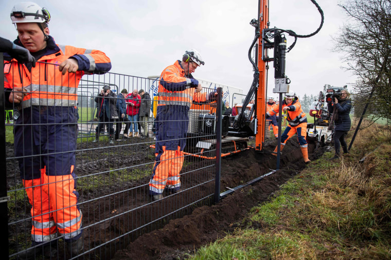 Image: Workers set up a fence at the Denmark-Germany border