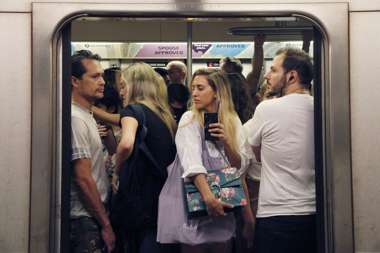 Commuters crowd into a subway car at the 1st Avenue L train station