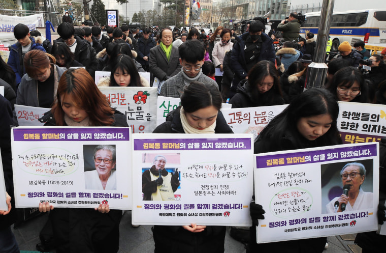 Mourners hold pictures of Kim Bok-dong during a moment of silence at a weekly rally near the Japanese Embassy in Seoul, on Jan. 30, 2019.