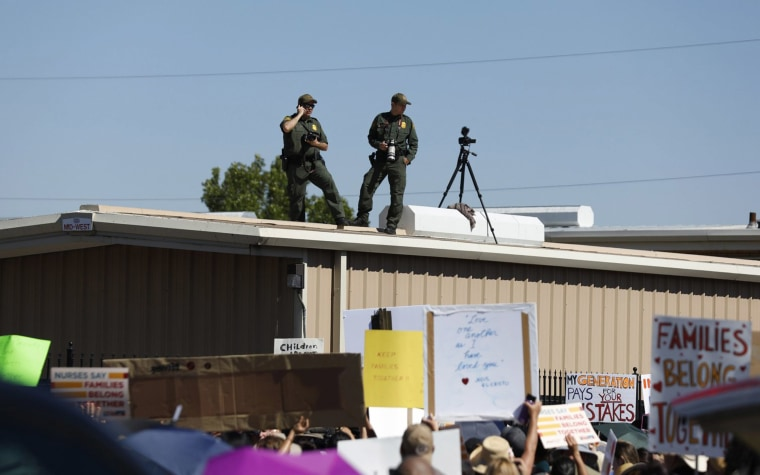 Image: U.S. Border Patrol agents watch as they take photos and video of the crowd protesting outside the U.S. Immigration and Customs Enforcement processing center in El Paso