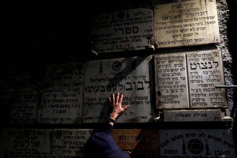 "Image: A man touches a gravestone commemorating the Jewish villages and towns whose communities were wiped out by the Nazis, inside ""The Chamber of the Holocaust"", in Jerusalem's Mount Zion"