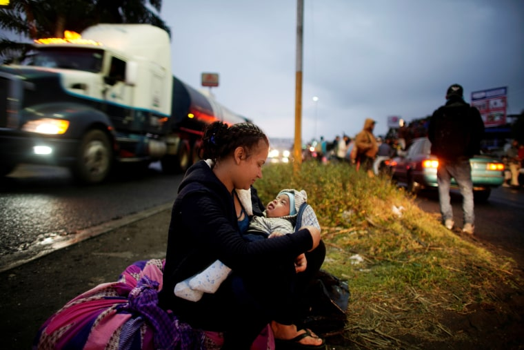 Image: Migrant Marely Villatoro, 20, from Honduras, plays with her 4 months-old child as she waits for a lift during their journey towards the United States, in Tierra Blanca, Mexico