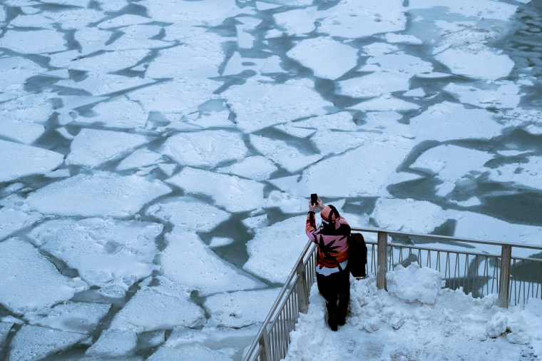 Image: A pedestrian stops to take a photo by Chicago River as bitter cold phenomenon called the polar vortex has descended on much of the central and eastern United States