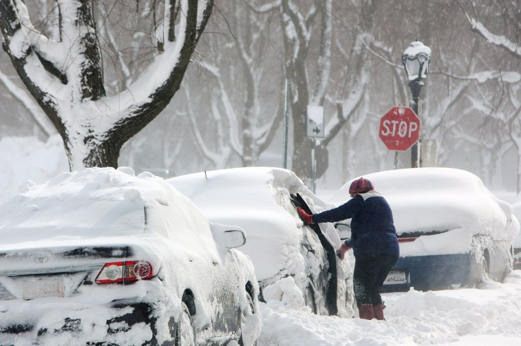 Image: A woman clears a car in the snow during a winter storm in Buffalo, New York