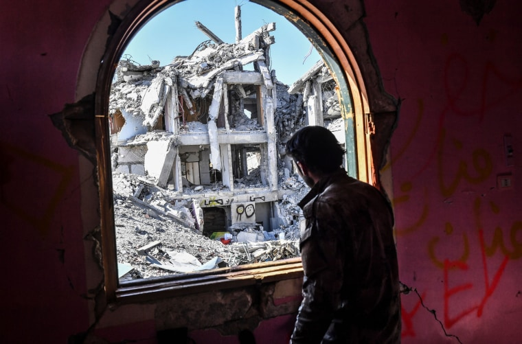 Image: A soldier with the Syrian Democratic Forces looks out on a damaged building in Raqqa, Syria, on Oct. 16, 2017.