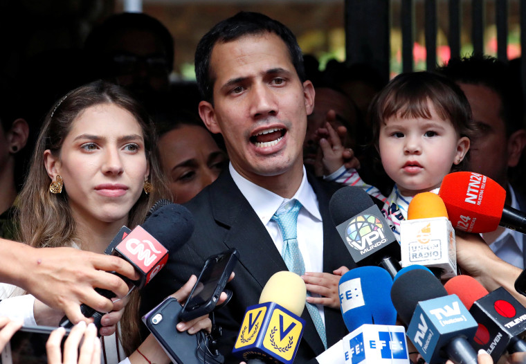 Image: Venezuelan opposition leader and self-proclaimed interim president Juan Guaido talks to media next to his wife Fabiana Rosales, while carrying their daughter outside their home in Caracas
