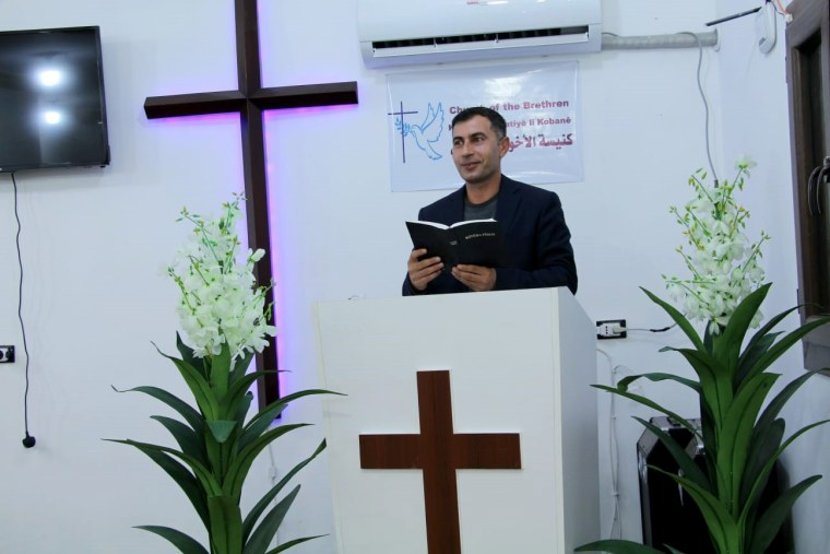 Image: Omar reads the Bible at the Church of the Brethren