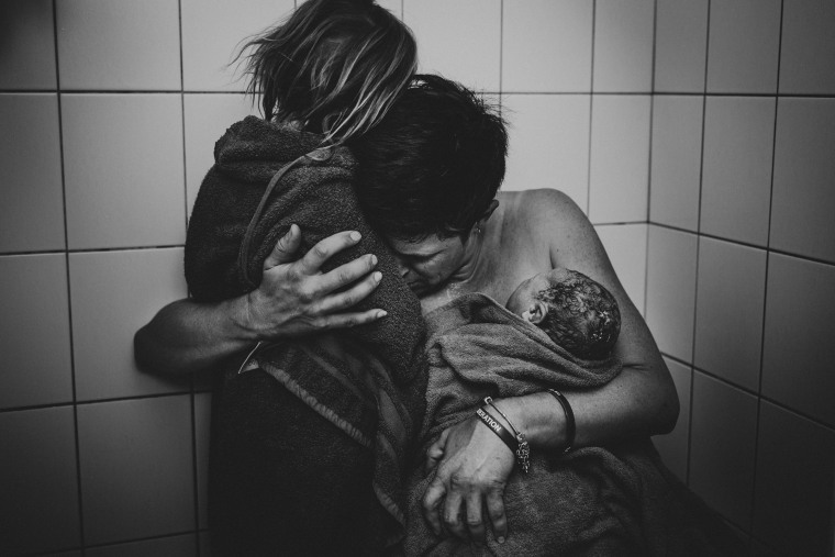 After labor a mom holds two of her children wrapped in towels. This image won second place for black and white photography.
