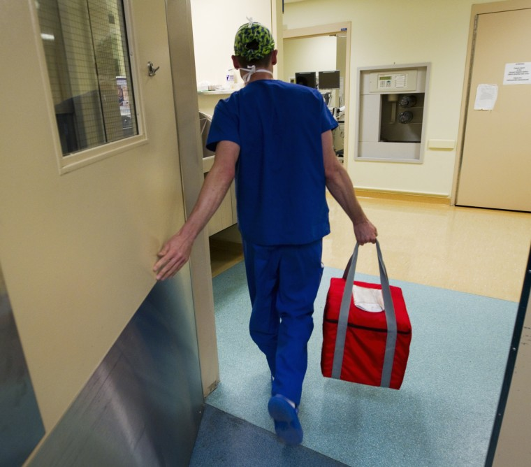 A nurse carries a cooler containing a section of donated liver to a waiting recipient.
