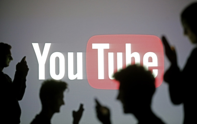 Image: Silhouette of people on mobile phones in front a YouTube sign