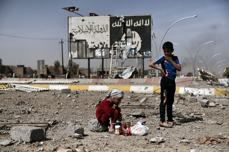 Image: Iraqi children in the Nablus neighborhood of Mosul, Iraq, near an Islamic State billboard on March 12, 2017.