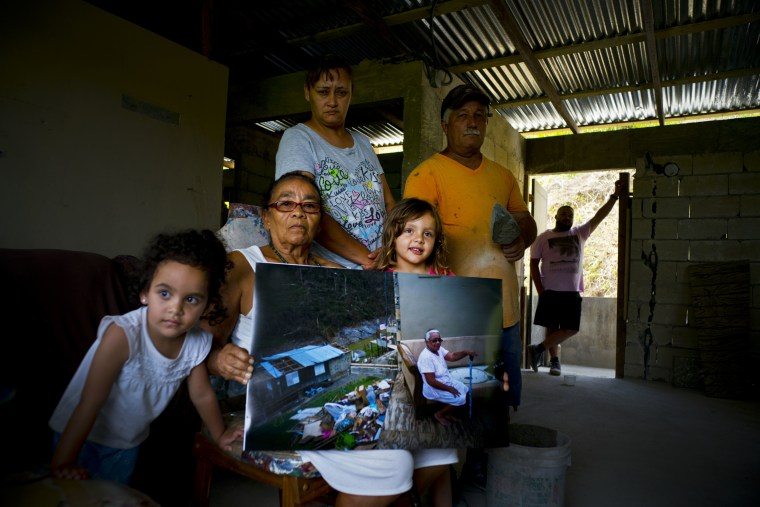 Image: Juana Sostre Vazquez holds a photo of her taken after Hurricane Maria destroyed her home on May 26, 2018.