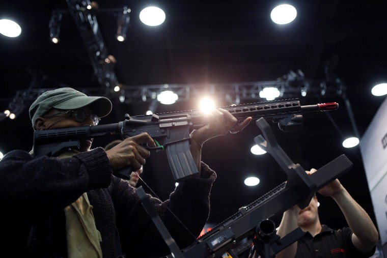 Image: An attendee holds an AR-15 style gun on the exhibit floor at the National Rifle Association's annual meeting in Louisville, Kentucky, on May 20, 2016.