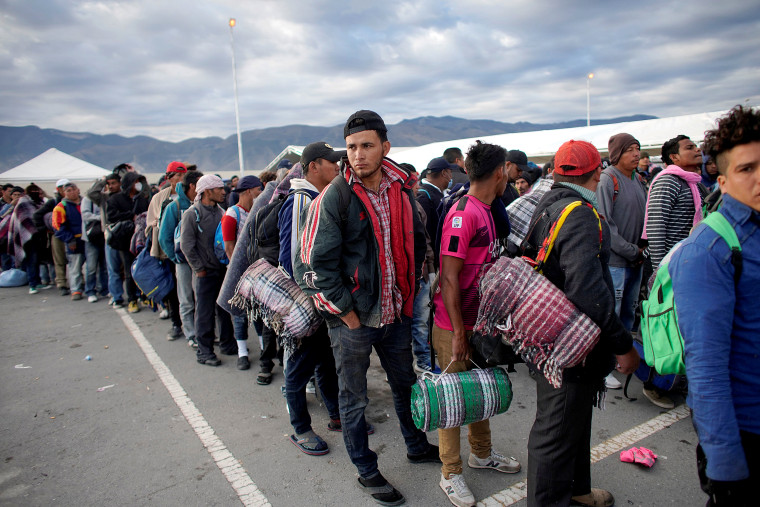Image: Migrants wait in line to get into buses during their journey towards the United States, in Saltillo