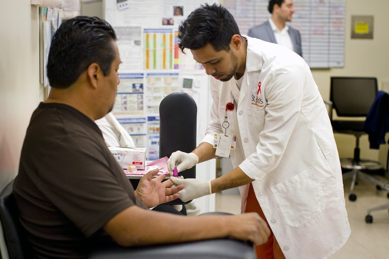LOS ANGELES, CA -MARCH 18, 2014: Medical Assistant Hector Reyes administers an HIV blood test to pat