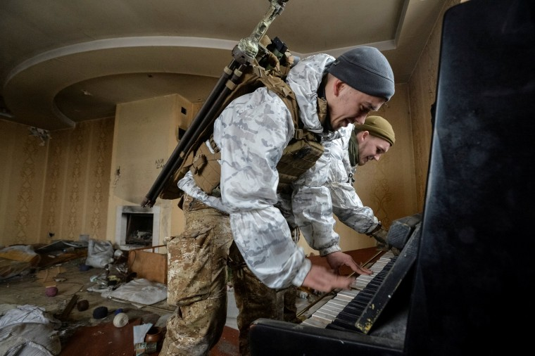 Image: Members of the Ukrainian Armed Forces play the piano in -? destroyed house near their position on the front line in Donetsk Region