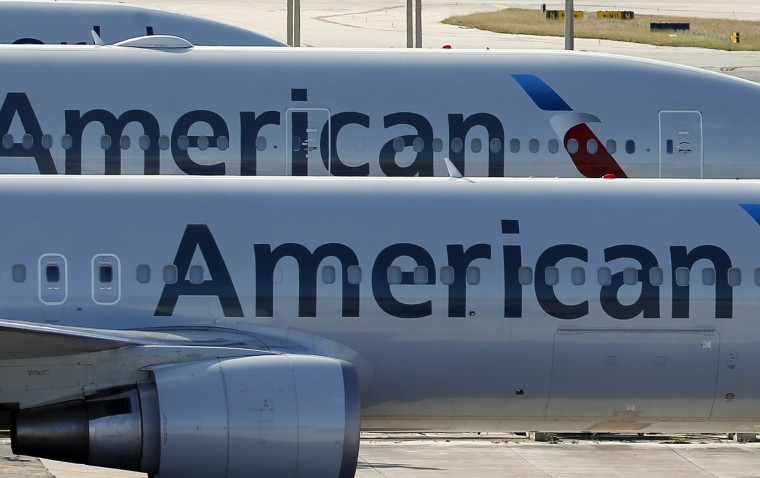 Image: A pair of American Airlines jets are shown parked on an airport apron
