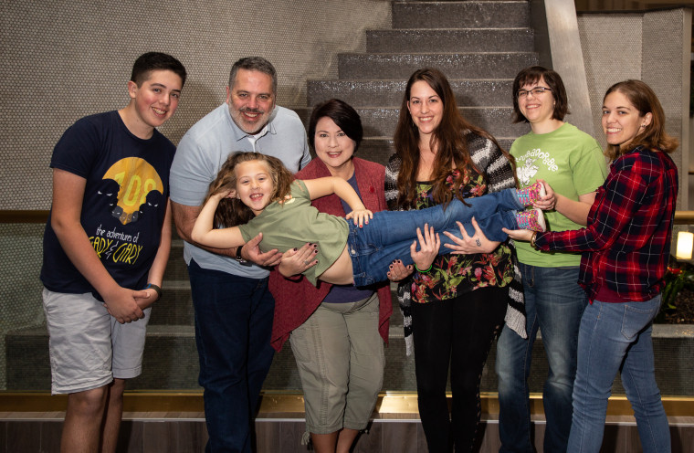Ted, his wife Susan and their children Ethan and Olivia pose with Ted's biological children through sperm donorship, Melissa Daniels, Hannah Maitland and Alexandra Cheshire.