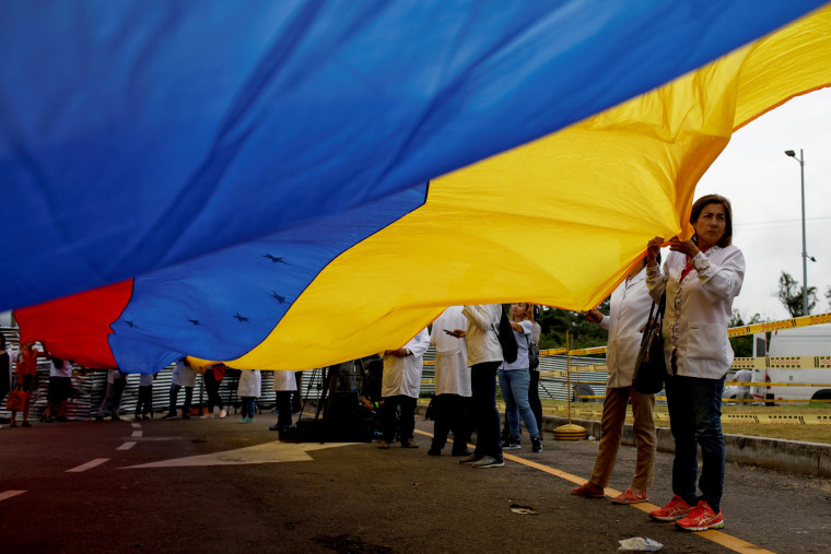 Image: Venezuelan doctors hold a flag during a protest at a blockade on a border bridge in Cucuta, Colombia, on Feb. 10, 2019.
