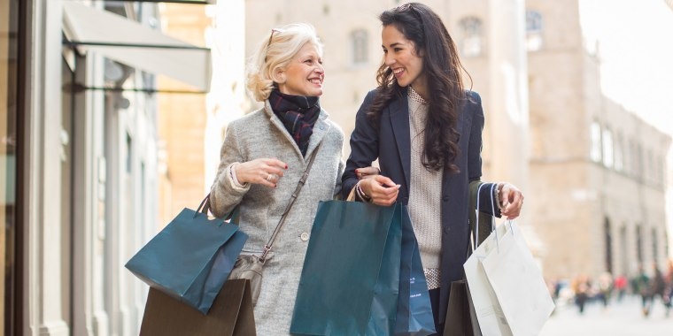 Mother and daughter in street carrying shopping bags face to face smiling
