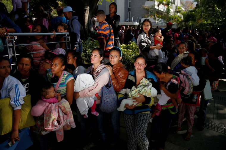 Image: Women carrying babies wait as they try to buy diapers outside a pharmacy in Caracas, March 18, 2017.