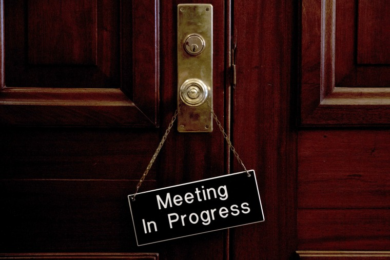 "Image: A sign that reads ""Meeting In Progress"" hands on a door of a closed meeting room at the Capitol as bipartisan House and Senate bargainers trying to negotiate a border security compromise"