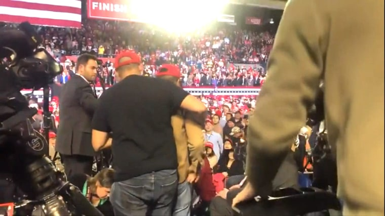 Image: A man is escorted from a Donald Trump rally in El Paso, Texas, after allegedly attacking a member of the media in attendance