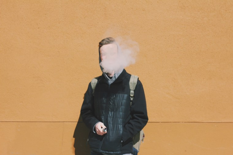 Young Man Smoking While Standing Against Wall On Sunny Day