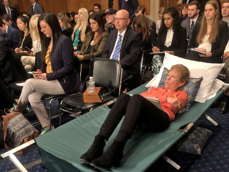 A woman testifies from a cot at Senate hearing on managing pain during the opioid crisis on Feb. 12, 2019.