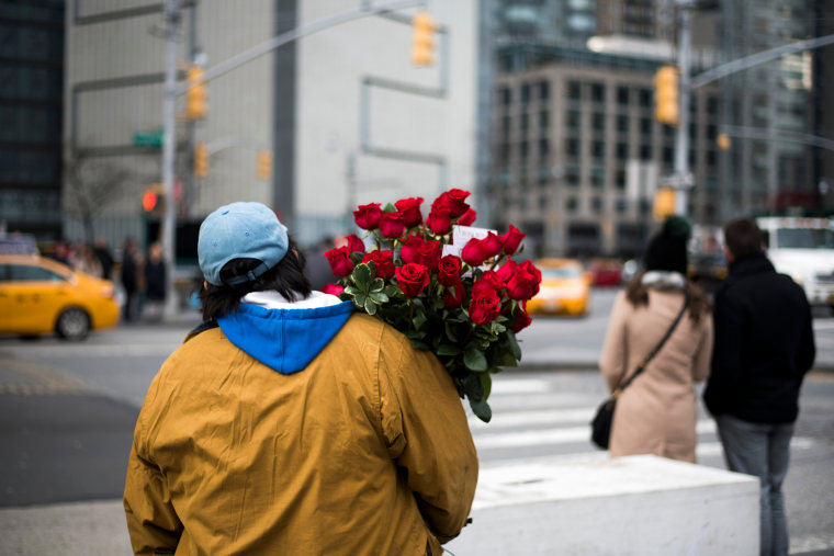 Image: A man crosses a street with a bouquet of roses on Valentine's Day in New York in 2018.