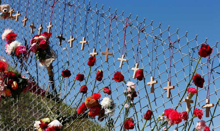 Image: Flowers and crosses line a fence near the school on a makeshift memorial for the victims of the Marjory Stoneman Douglas High School shooting in Parkland, Florida