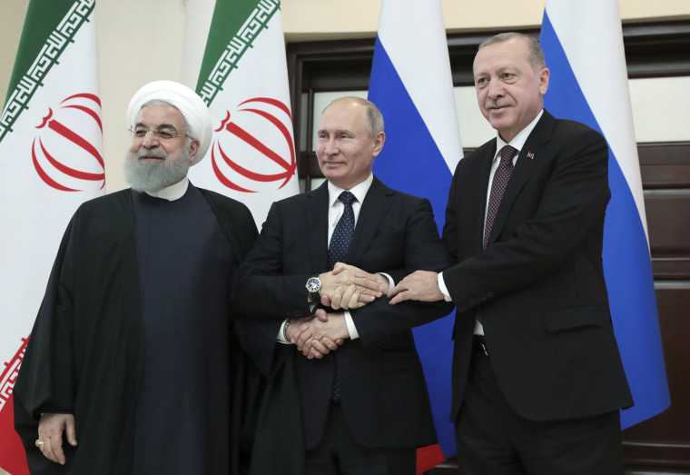 Image: Iranian President Hassan Rouhani, shakes hands with Turkish President Recep Tayyip Erdogan and Russian President Vladimir Putin during a meeting in Sochi, Russia, on Feb. 14, 2019.