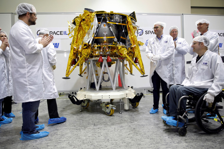 Members of Israeli non-profit group SpaceIL and representatives from Israel Aerospace Industries (IAI) stand next to an unmanned spacecraft during a presentation to the media in Yehud, Israel