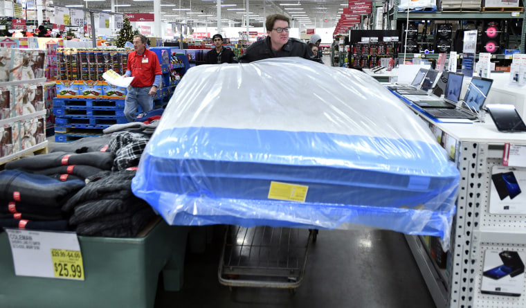 Image: BJ's Wholesale Club member David Carey of Shrewsbury, Mass., wheels a new mattress toward the checkout counter in Northborough