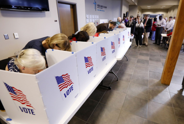 A growing line of voters, right, wait as others fill out their paper ballots in privacy voting booths on Nov. 6, 2018, in Ridgeland, Mississippi.