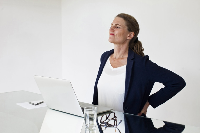 Image: Tired businesswoman suffering backache while working at office desk