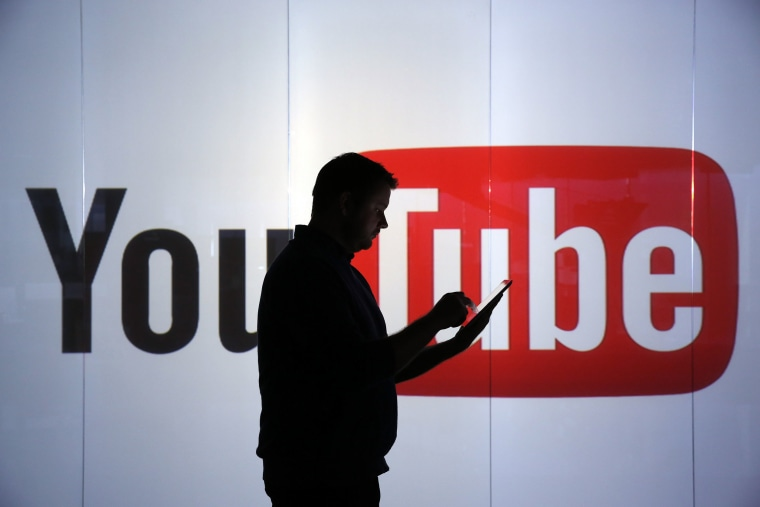 Image: A man checks a mobile device whilst standing against an illuminated wall bearing YouTube Inc.'s logo