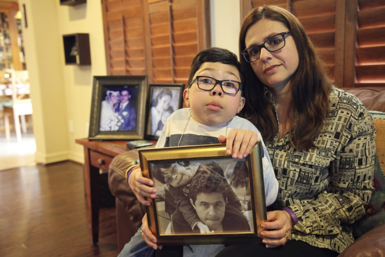 Image: Sergio Cardenas holds a photo of him and his father, detained Citgo executive Gustavo Cardenas, while sitting with his mother, Maria Elena, at their home in Katy, Texas, on Feb. 15, 2019