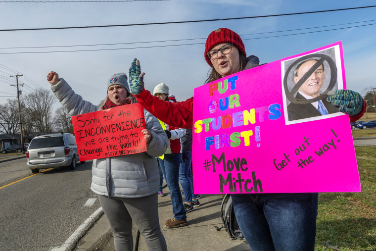 Image: Cabell County schoolteachers Ginny Noble, right, and Kayla Massie demonstrate outside of Hurricane High School on the first day of a statewide teachers strike in West Virginia on Feb. 19, 2019.