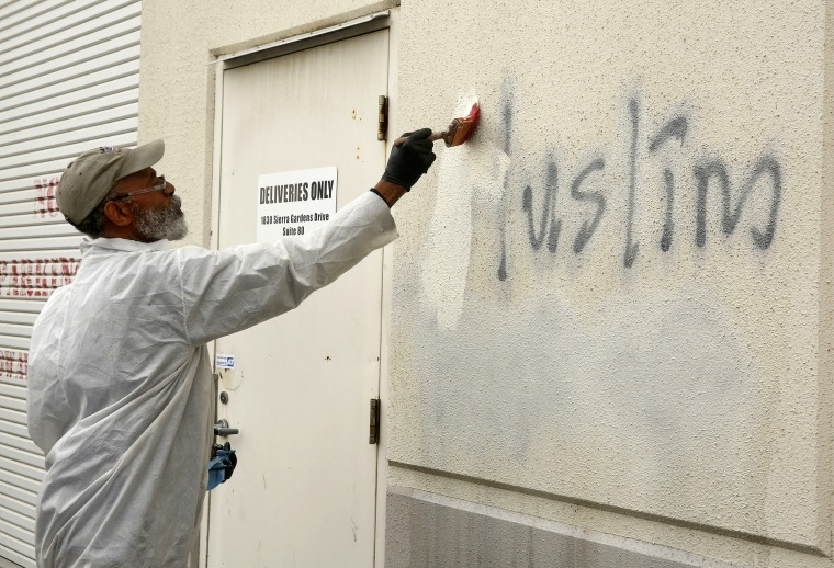 Willie Lawson paints over racist graffiti on the side of a mosque in what officials called an apparent hate crime on Feb. 1, 2017, in Roseville, California.
